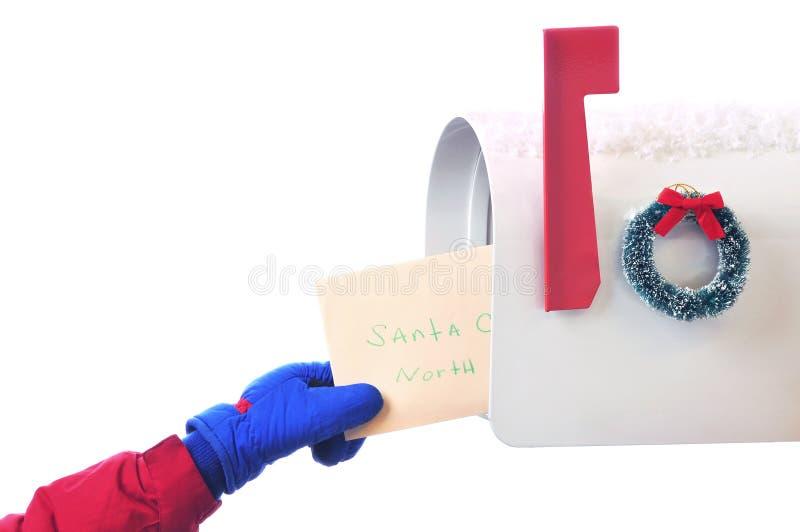 Mano di Childs che dispone lettera nella cassetta postale isolata immagini stock libere da diritti