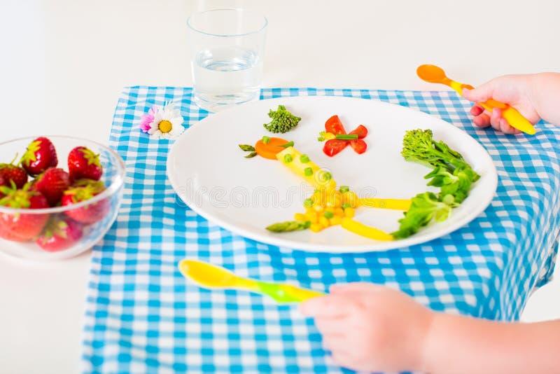 Mano di Childs e pranzo di verdure sano per i bambini l immagini stock libere da diritti