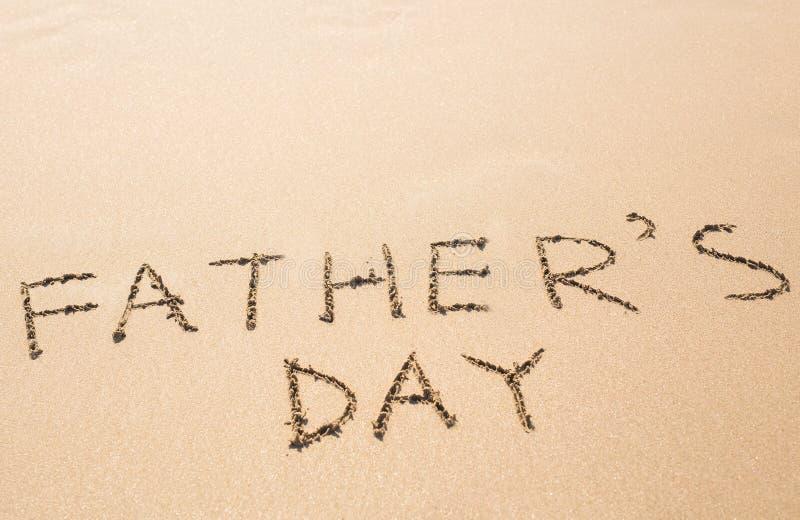 Mano di festa del papà scritta nella spiaggia sabbiosa fotografie stock libere da diritti
