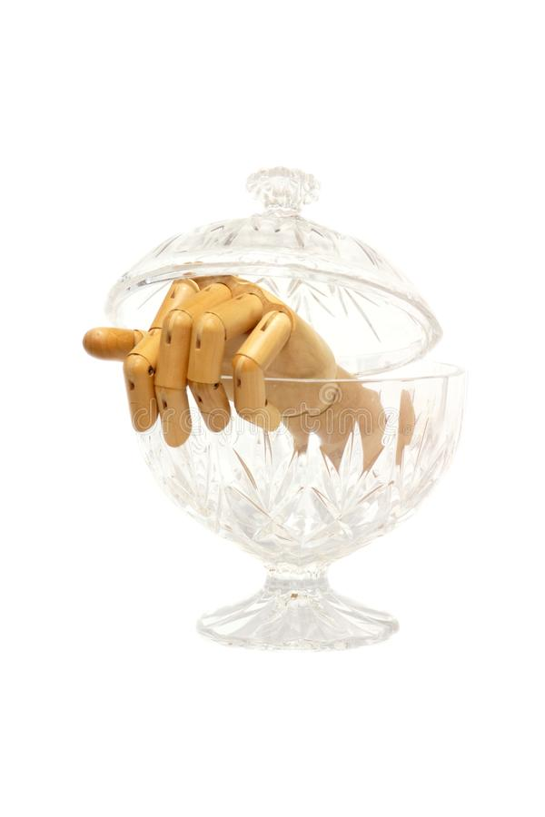 Mano di legno articolata che esce da una scatola di vetro dei confectionerys fotografia stock