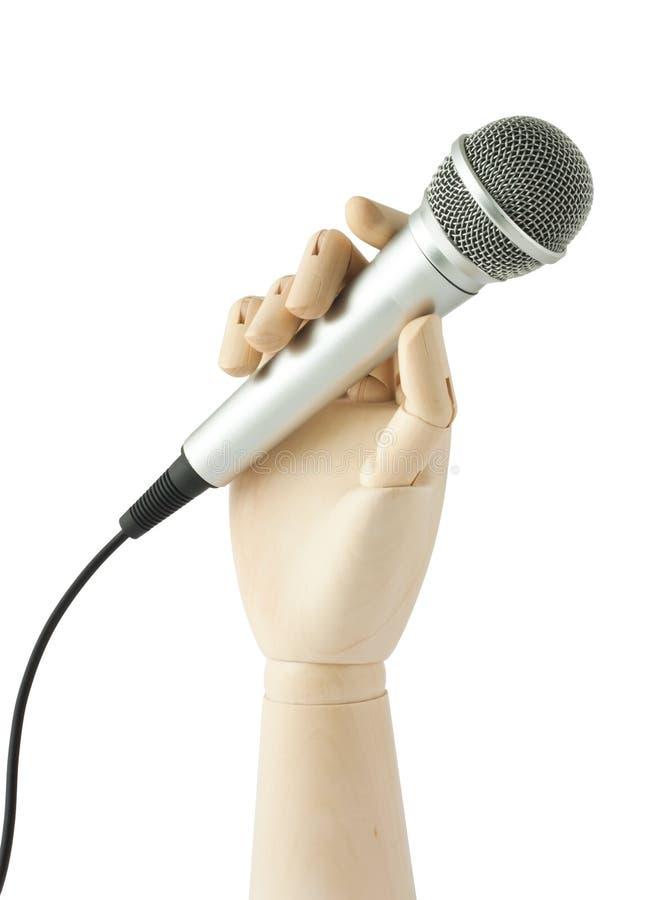 Mano di legno che tiene un microfono immagini stock