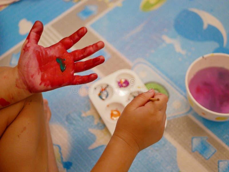 Mano di piccolo bambino che è dipinto con i colori rossi e verdi - handprint del bambino/pittura dell'impronta digitale immagini stock