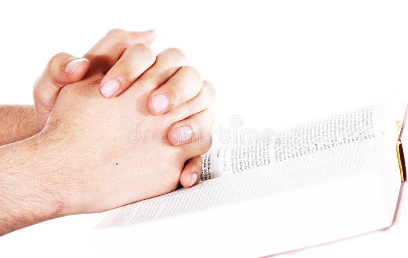 Mano di preghiera su una bibbia aperta fotografia stock