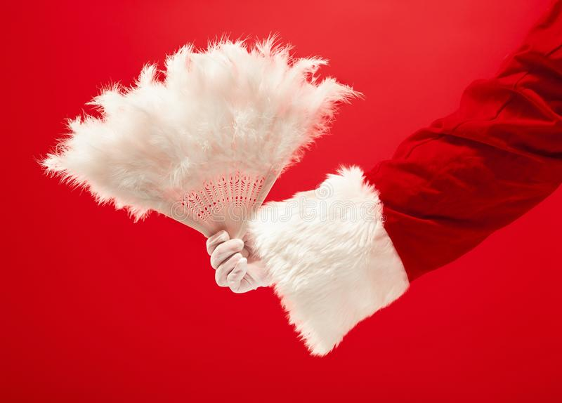Mano di Santa Claus che tiene fan di Natale del giocattolo un retro su fondo rosso fotografie stock libere da diritti