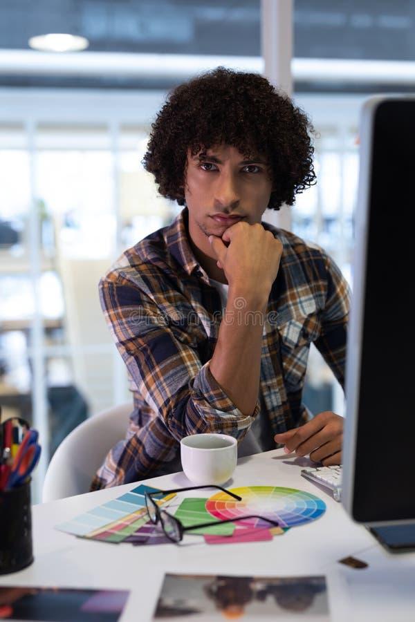 Mano di seduta del grafico maschio sul mento fotografia stock libera da diritti