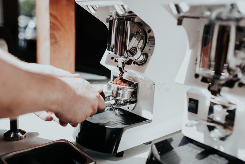 Mano di un barista che produce caffè facendo uso di una macchina del caffè ad un caffè immagine stock libera da diritti
