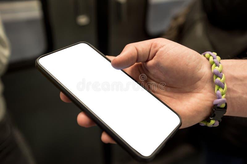 Mano di un ragazzo con braccialetto che tiene in mano un cellulare nella metropolitana con schermo bianco immagine stock libera da diritti