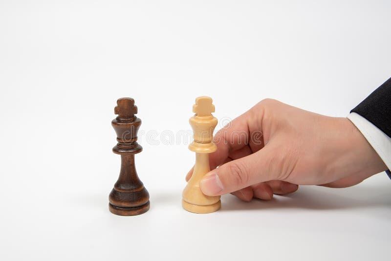 Mano di un uomo d'affari commovente che tiene un pezzo degli scacchi di re Concetto di negoziato di affari fotografie stock libere da diritti