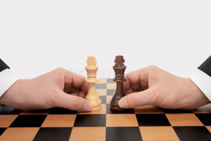Mano di un uomo d'affari commovente che tiene un pezzo degli scacchi di re Concetto di negoziato di affari immagine stock
