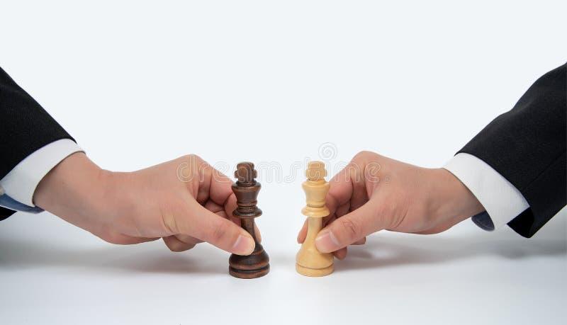 Mano di un uomo d'affari commovente che tiene un pezzo degli scacchi di re Concetto di negoziato di affari fotografia stock