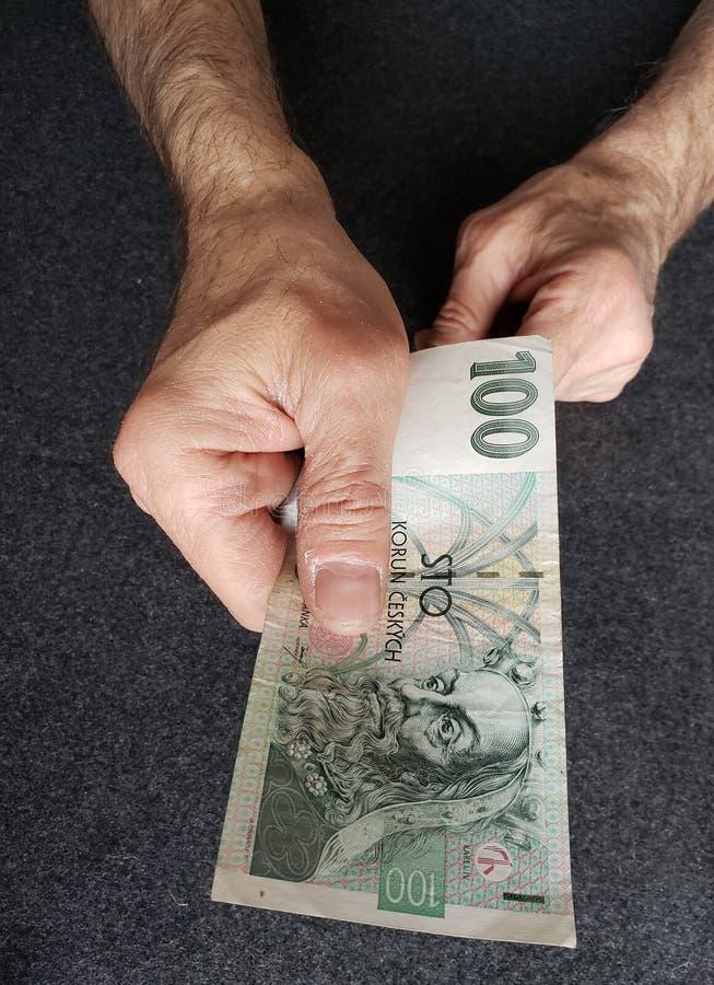 mano di un uomo più anziano che tiene una banconota ceca di korun 100 fotografia stock libera da diritti