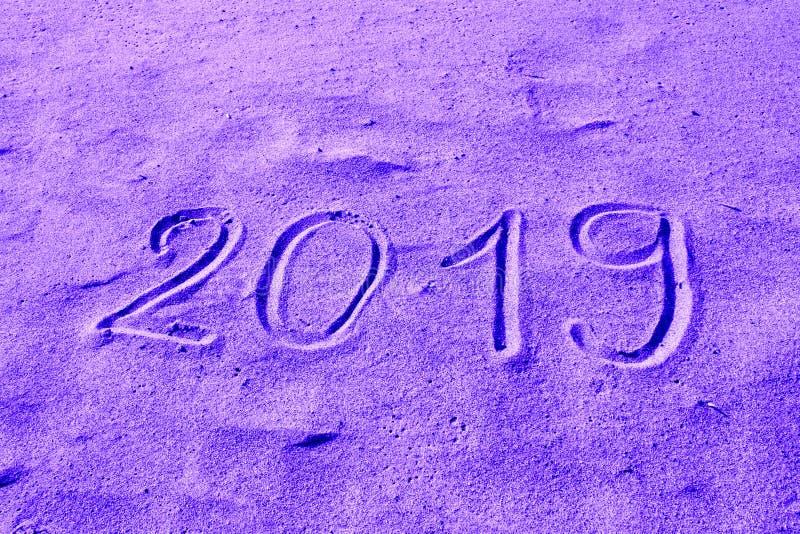 mano 2019 dibujada en la arena coloreada en púrpura El Año Nuevo está viniendo o los días de fiesta catalogan diseño abstracto de fotos de archivo