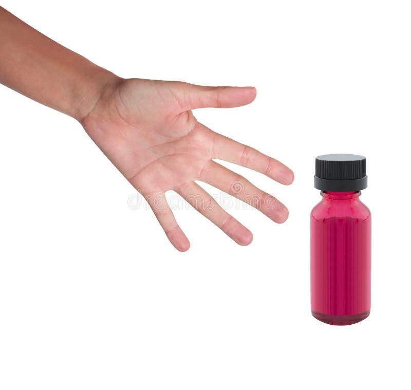 Mano e una bottiglia della medicina su bianco fotografia stock