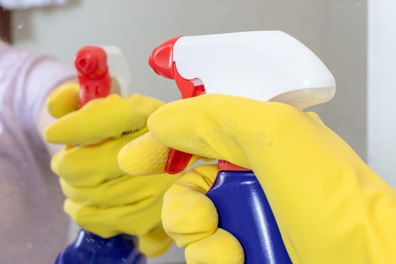 Mano en el guante de goma amarillo que sostiene una botella de limpieza azul del espray lista para limpiar un espejo Lavando, lim foto de archivo libre de regalías