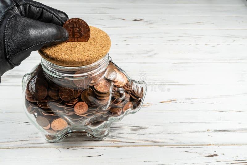Mano en el guante que sostiene un Bitcoin sobre una hucha de cristal Concepto imágenes de archivo libres de regalías