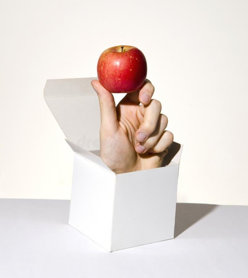 Mano en el rectángulo que sostiene la manzana imagen de archivo