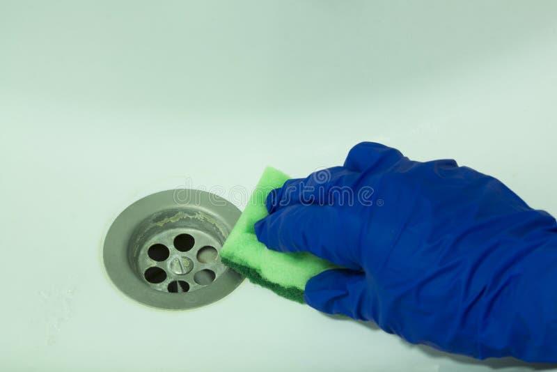 Mano en guantes azules de la seguridad con una esponja que limpia un fregadero del baño foto de archivo