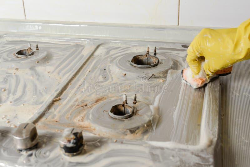 Mano en los guantes amarillos que lavan la estufa de gas fotografía de archivo libre de regalías