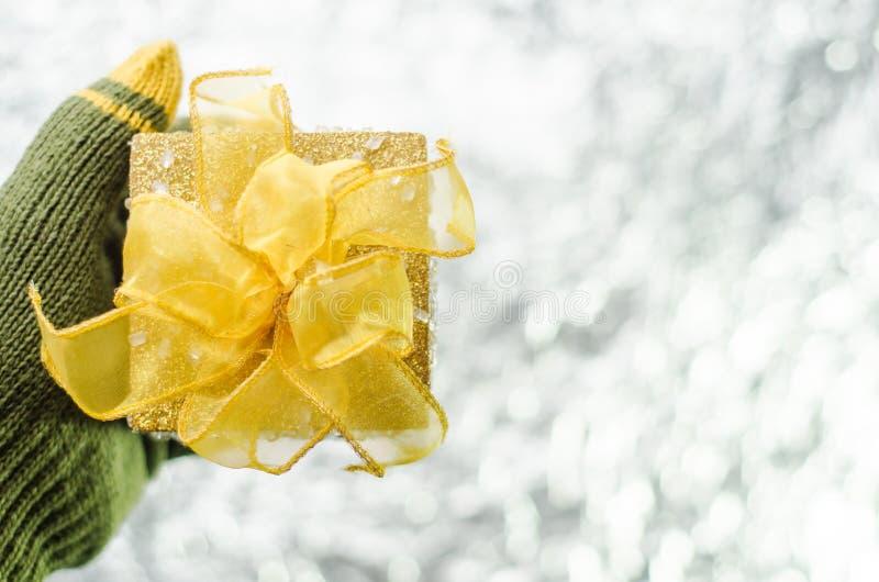 Mano en los guantes que sostienen la caja de regalo de la Navidad del oro imágenes de archivo libres de regalías