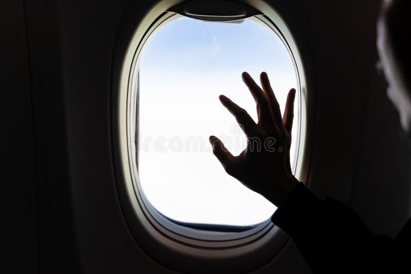 Mano en ventana del aeroplano con la vista aérea de las nubes blancas con mirada de la cara del hombre de la silueta afuera imagen de archivo