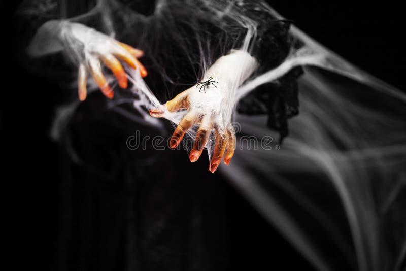 Mano espeluznante de Halloween en anaranjado y blanco con la web de araña, mano del zombi imagen de archivo