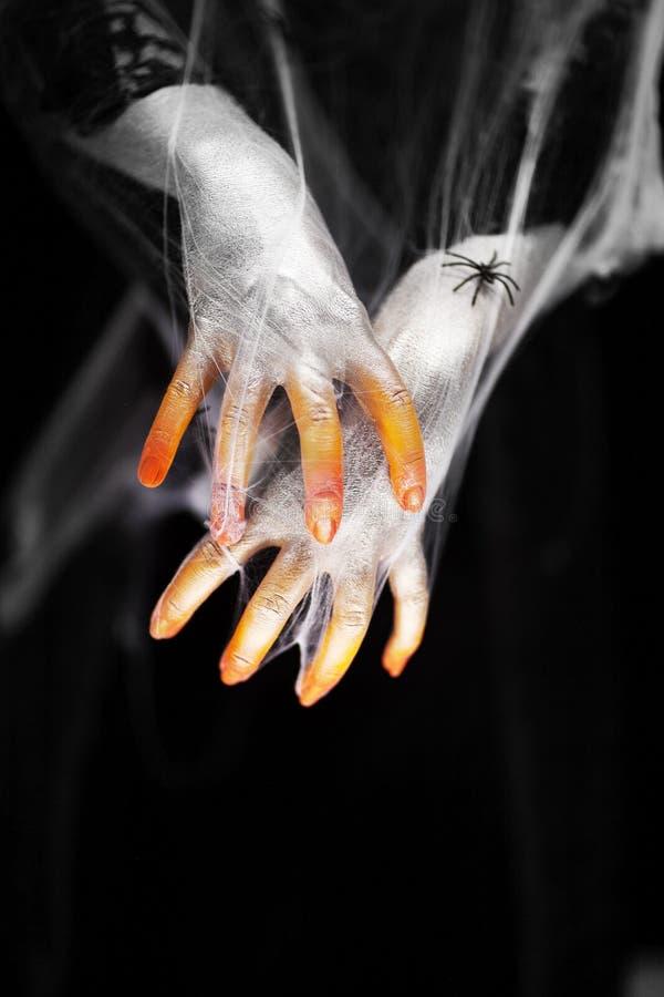 Mano espeluznante de Halloween en anaranjado y blanco con la web de araña, mano del zombi fotografía de archivo