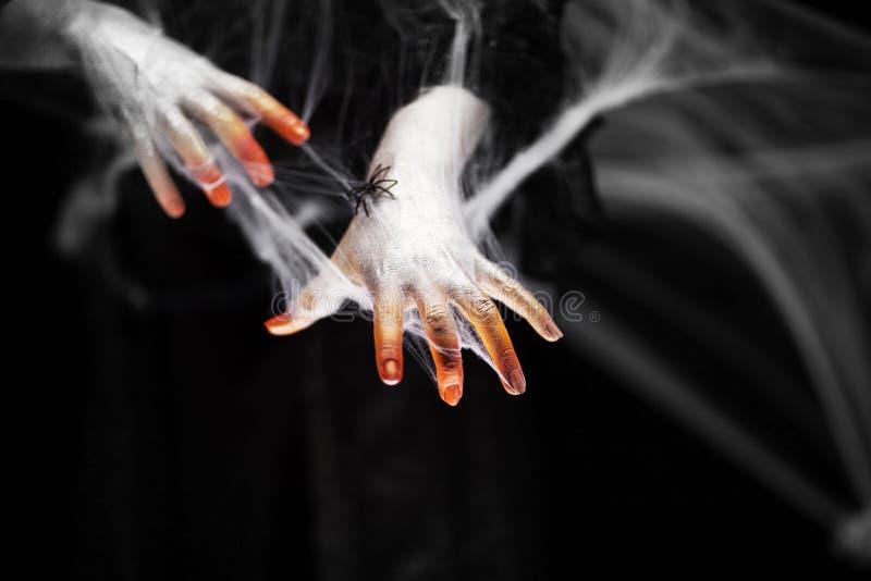 Mano espeluznante de Halloween en anaranjado y blanco con la web de araña, mano del zombi fotos de archivo