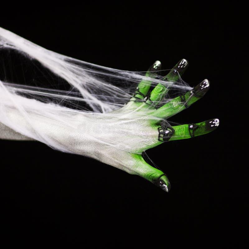 Mano espeluznante de Halloween en verde y blanco con la web de araña, zombi imagen de archivo