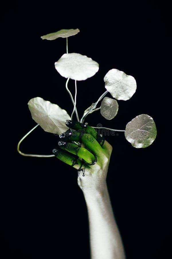 Mano espeluznante de Halloween en verde y de plata con la planta imagen de archivo libre de regalías