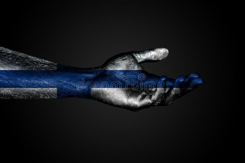 Mano extendida con una bandera exhausta de Finlandia, una muestra de la ayuda o una petici?n, en un fondo oscuro imagenes de archivo