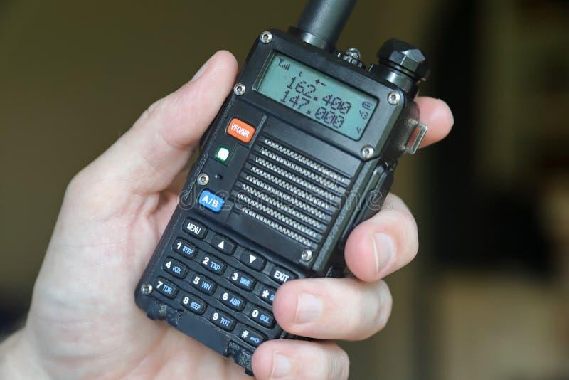 Mano facendo uso del walkie-talkie del radioamatore fotografie stock