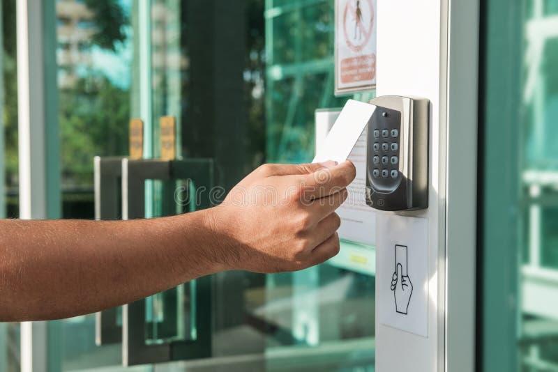 Mano facendo uso dell'esame della carta chiave di sicurezza per aprire la porta ad entrare in costruzione privata Sistema di sicu fotografia stock
