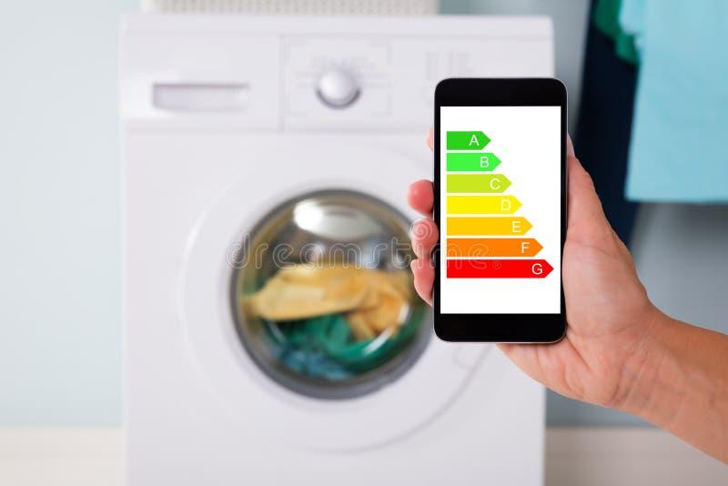 Mano facendo uso dell'etichetta di energia sul telefono cellulare contro la lavatrice fotografia stock