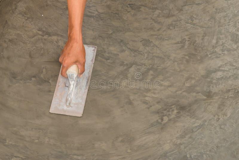 Mano facendo uso della cazzuola d'acciaio per finire superficie di calcestruzzo bagnata lucidata immagine stock libera da diritti