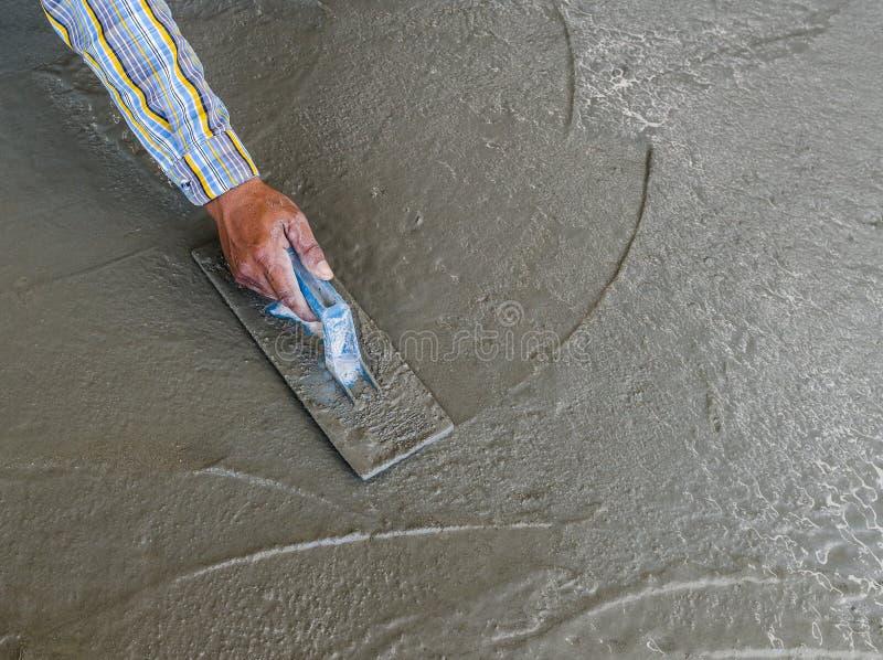 Mano facendo uso della cazzuola per finire pavimento di calcestruzzo bagnato fotografie stock libere da diritti