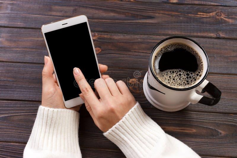 Mano facendo uso dello schermo bianco del telefono sulla vista superiore fotografie stock libere da diritti