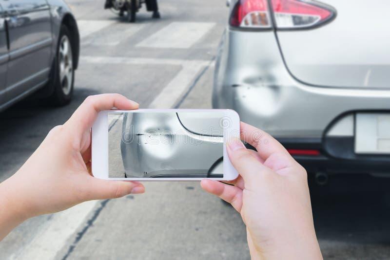 Mano facendo uso dello Smart Phone mobile che prende foto dell'incidente di incidente stradale fotografia stock libera da diritti