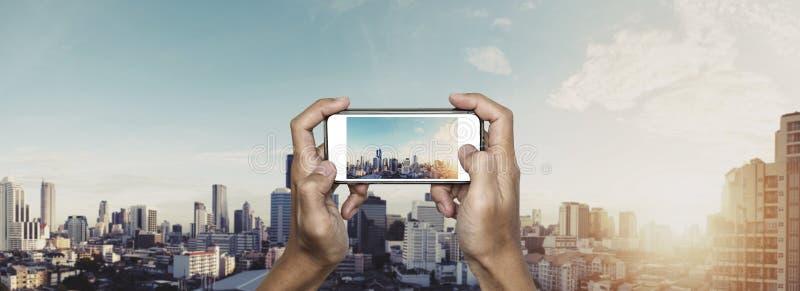 Mano facendo uso dello smartphone che prende foto della città di Bangkok nell'alba fotografia stock