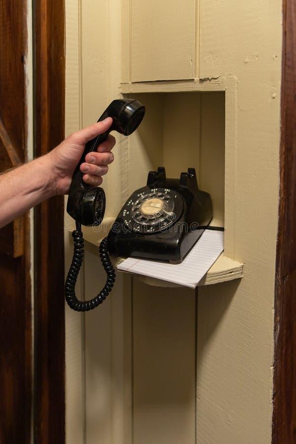 Mano facendo uso di vecchio telefono rotatorio che si siede nell'angolo nel corridoio immagine stock libera da diritti