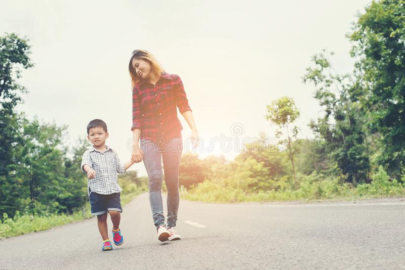 Mano felice della tenuta della mamma con suo figlio che cammina sulla via immagini stock libere da diritti