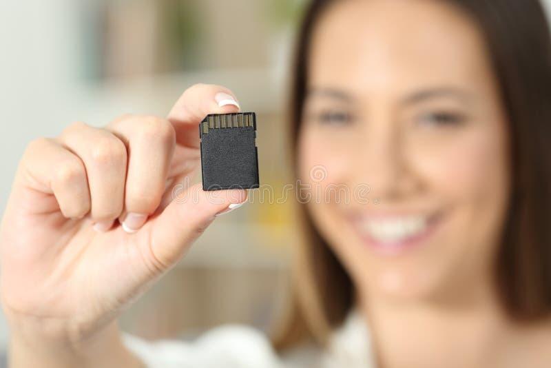 Mano feliz de la mujer que muestra una tarjeta de memoria fotos de archivo libres de regalías