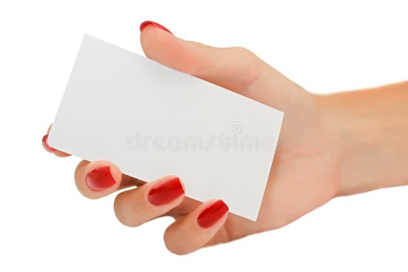 Mano femenina agradable que sostiene una tarjeta de visita en blanco imagen de archivo libre de regalías
