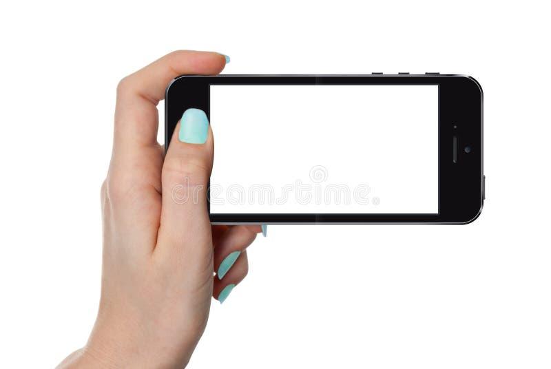 Mano femenina aislada que sostiene el teléfono elegante fotografía de archivo