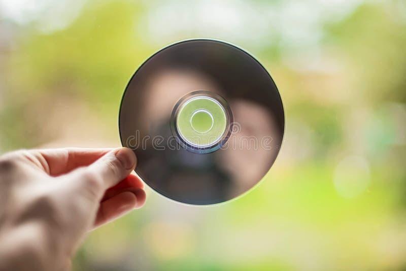 Mano femenina CD de la m?sica en fondo de la ventana fotos de archivo