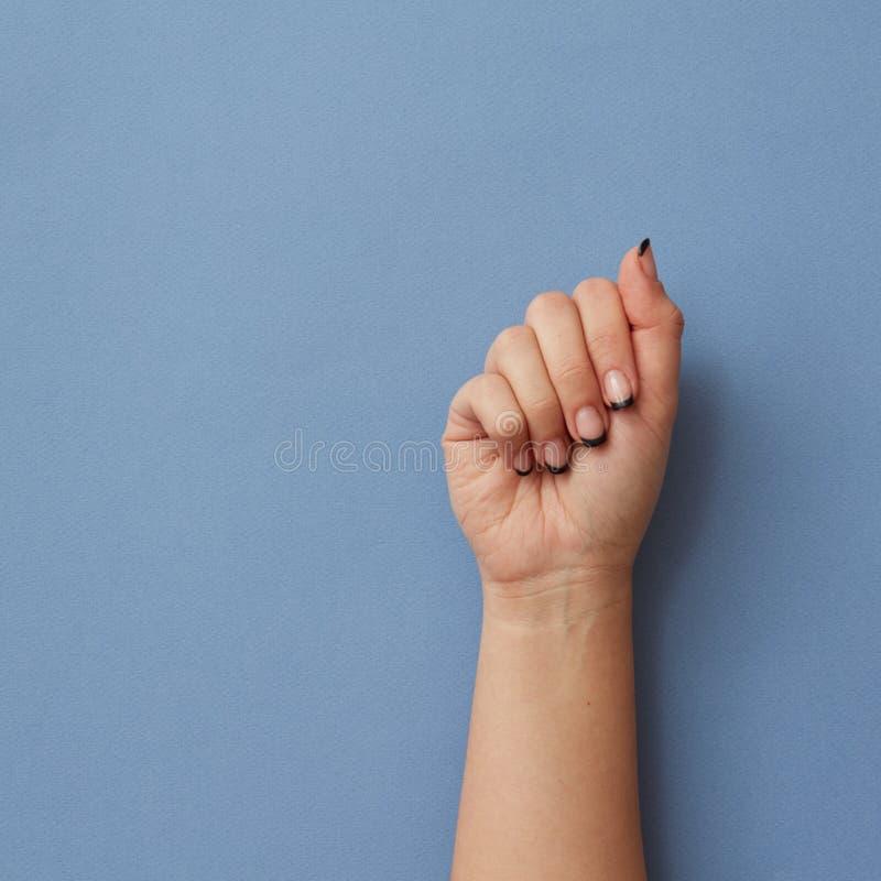 Mano femenina cerrada en fondo azul fotografía de archivo libre de regalías