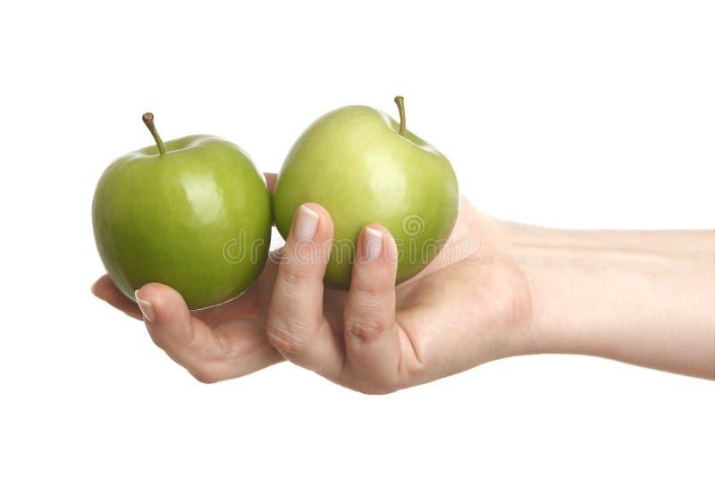 Mano femenina con dos manzanas verdes fotografía de archivo libre de regalías