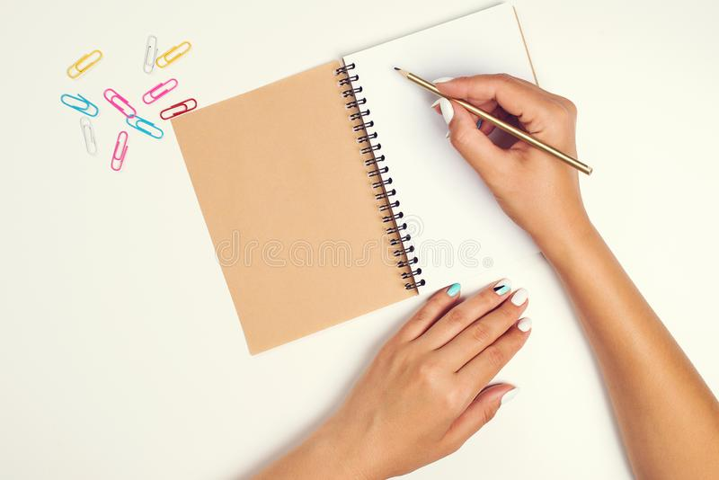 Mano femenina con el lápiz Hoja de papel blanca en el escritorio Cuaderno Vista superior del escritorio del trabajo Maqueta para  fotografía de archivo libre de regalías