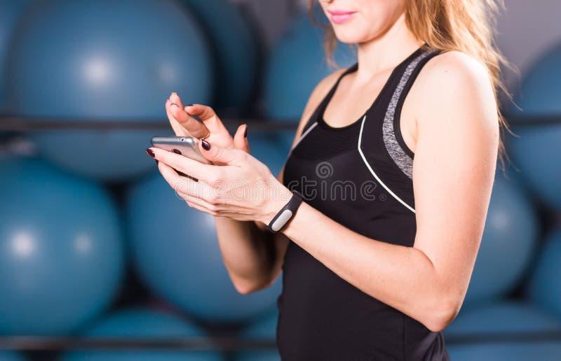 Mano femenina con el perseguidor de la aptitud en el cierre del gimnasio para arriba fotos de archivo libres de regalías