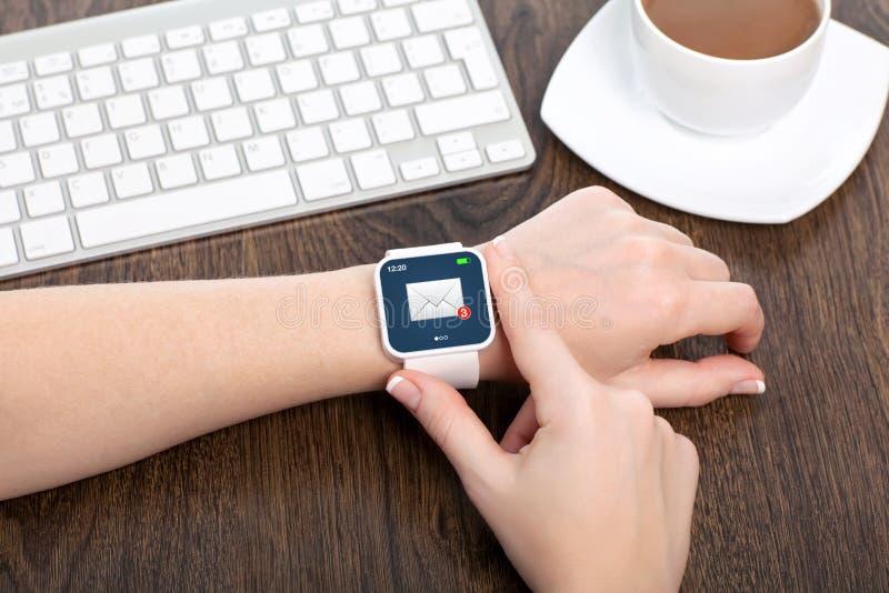 Mano femenina con el smartwatch con el correo electrónico fotos de archivo