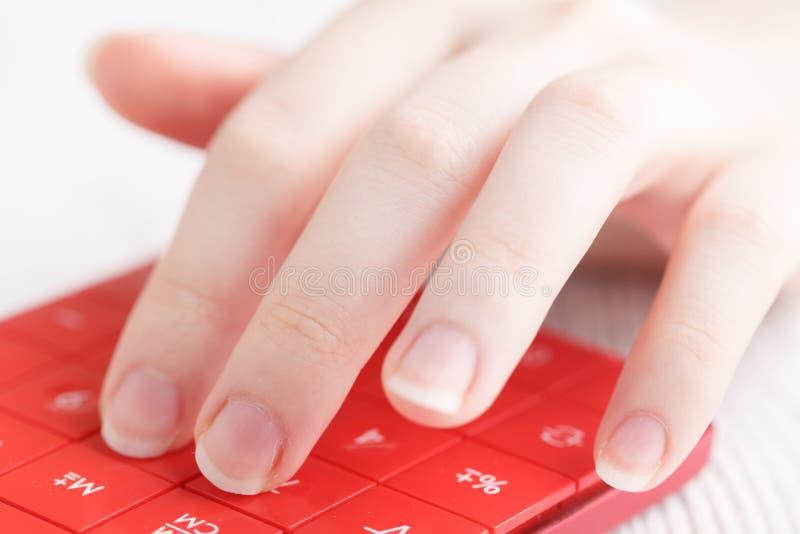 Mano femenina con la calculadora foto de archivo libre de regalías